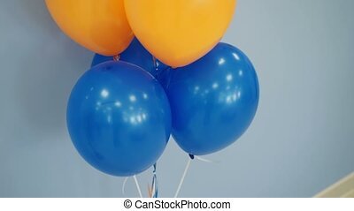 White, orange and blue balloons indoors