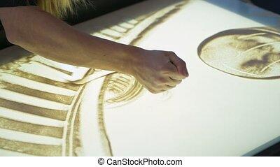 Artist paints picture using sand closeup