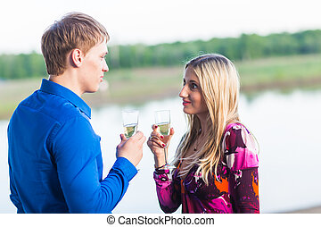 Couple drinking champagne outdoors enjoying their summer holidays.