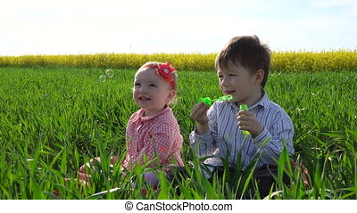 Little boy and girl are sitting in the field and blowing soap bubbles