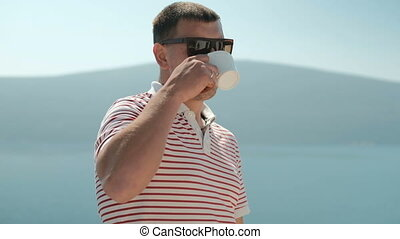 Attractive man drinks coffee and looks to distance outdoors....
