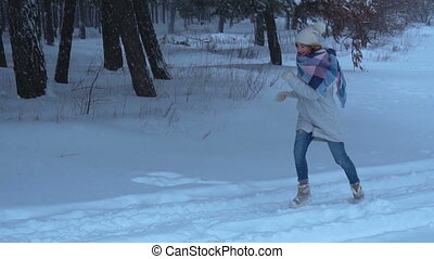 young girl is running through the snow in the Woods and...