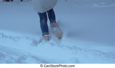 a girl runs across large snow drifts