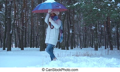girl smiling and dancing with umbrella in snow forest -...
