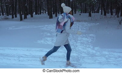 a cheerful girl in hat and scarf runs on snow road - a...