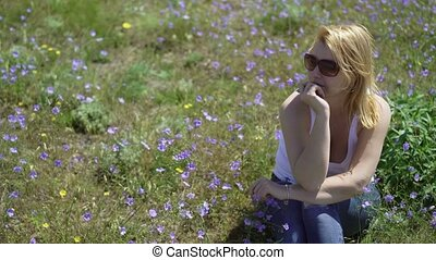 Young blonde woman sitting in a field