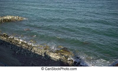 Waves on pebble beach at sunny day