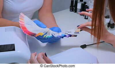 Nail technician shows the color palette of nail services in beauty salon.