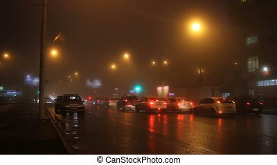 The lights of night city in fog and cars on road.