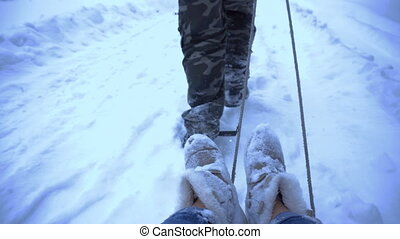 man rolls a girl on a sled - with a first-person view man...