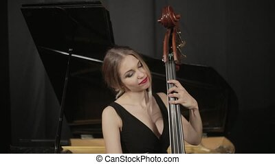 Girl in black dreess playing on the contrabass - Girl in...