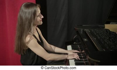 Girl in black dress playing on the piano