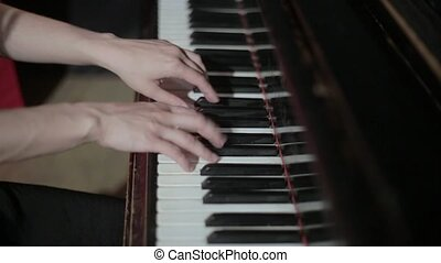Young woman playing on the piano
