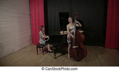 Two young women playing a musical instruments - Two girls...