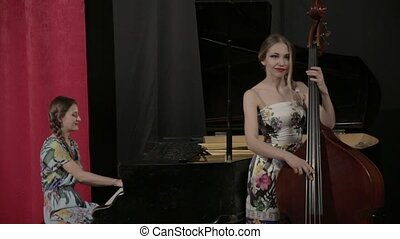Two young women playing a musical instruments