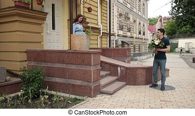Romantic man giving flowers to his girlfriend - Young...