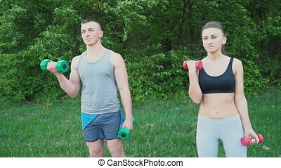 Couple practicing with a dumbbell - Young couple exercising...