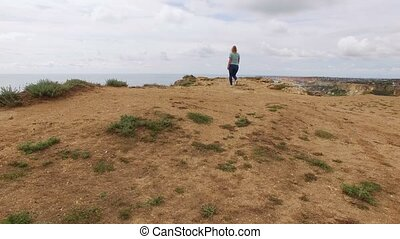 Young woman walks on a rock near sea aerial