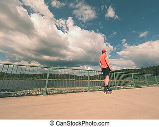 Rear view to inline skater in red t-shirt and black pants skating on the bridge . Outdoor inline skating