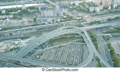 Aerial shot of city road interchange and moving commuter train. 4K clip