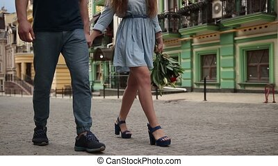 Couple's legs walking down the city street