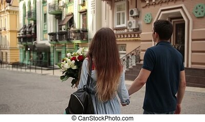 Affectionate couple walking down old city street