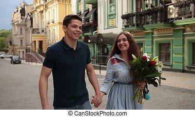 Romantic couple in love strolling down city street - Joyful...