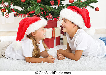Laughing kids in front of christmas tree