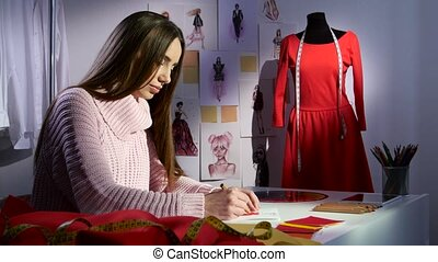 Fashion designer draws a sketch of a red dress, outside the window already evening