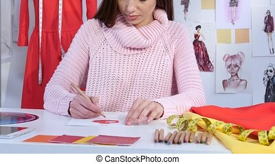 Girl designer draws a sketch of a dress on a table lie fabric samples. Close up