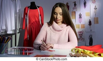 Fashion designer draws a sketch of a red dress, workshop -...