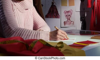 Hands designer draws a sketch of a dress, on a cloth table, for tailoring. Close up