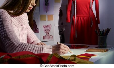 Designer draws a sketch in the background is a mannequin...