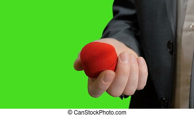 The groom opens the box with a wedding ring.Green screen
