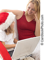 Woman and little girl playing with a laptop at christmas time