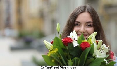 Portrait of smiling young woman smelling flowers - Portrait...