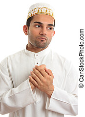 Ethnic man holding his hands to his chest - An ethnic man in...