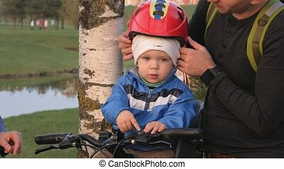 Parents dress a toddler with a bicycle helmet in the park. A boy is sitting in a child seat in front of a bicycle