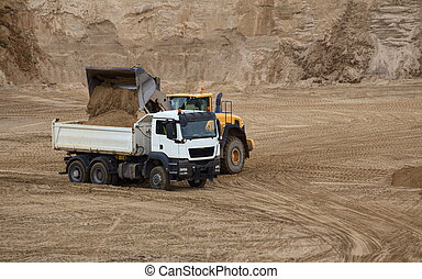 Truck and loader on an outcrop site.