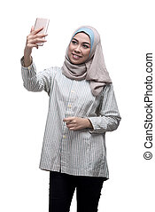 Happy asian muslim woman taking selfie picture with...