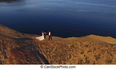 Bride and groom walking on mountain at sunset aerial