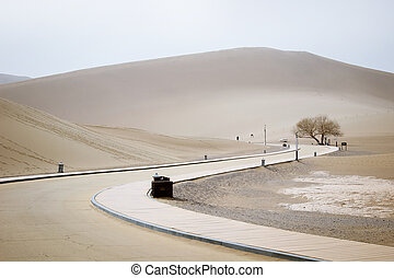 The road inside Mingsha shan desert and Crescent moon lake in Dunhuang, Gansu, China