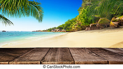 Tropical beach with wooden table, summer holiday background.