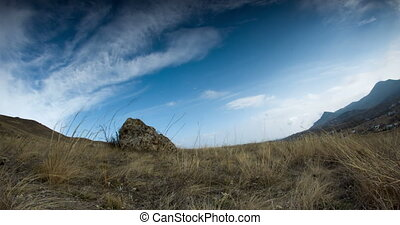 Clouds fly over a stone on a hill above the valley - The...