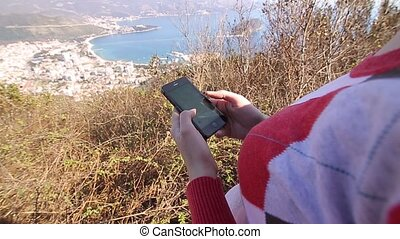 The tourist looks at the map on the smartphone. A girl on...