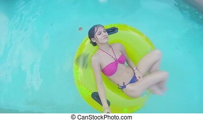 Young woman relaxing in a pool with yellow inflatable ring. Top of view.