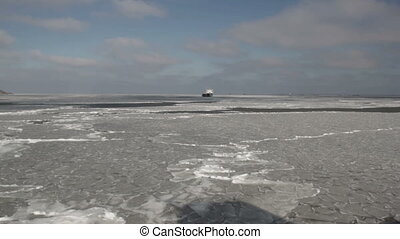 The ship is moving across the sea covered with ice