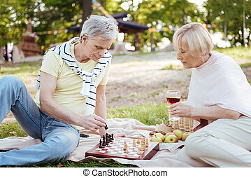 Involved retired couple playing chess in the park