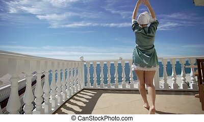 Young woman in bathrobe comes to balcony near sea