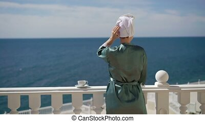 Young woman in bathrobe on balcony near sea